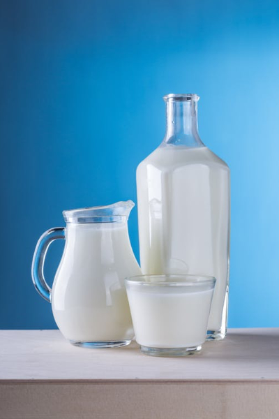 bottle, jar and cup of milk in front of a light blue background