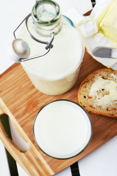 Bottle of milk and glass of milk on wooden stand with bread and butter